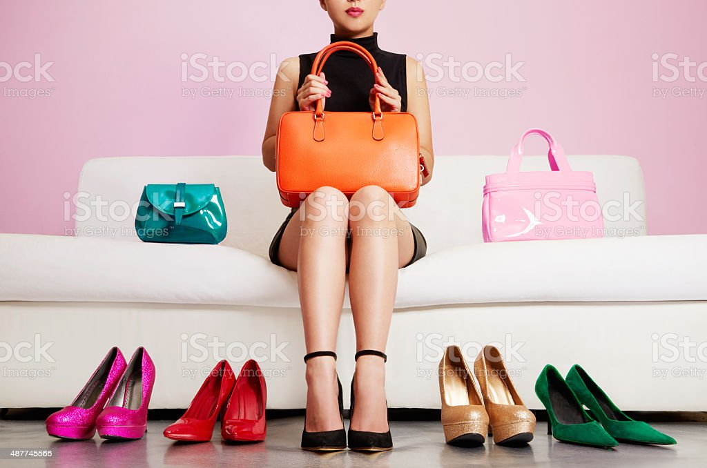Woman sitting on sofa with colorful shoes and bags. Shopping. - Royalty-free 2015 Stockfoto