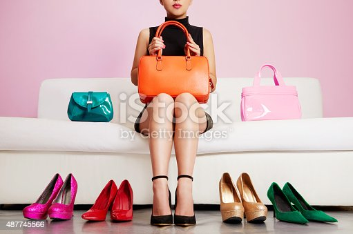istock Woman sitting on sofa with colorful shoes and bags. Shopping. 487745566