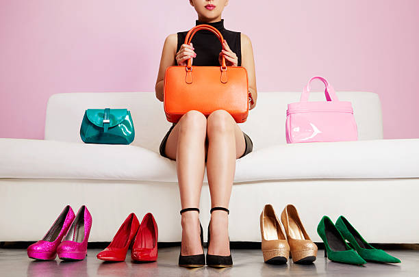 Woman sitting on sofa with colorful shoes and bags. Shopping. stock photo