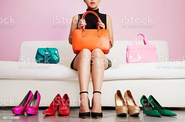 Woman Sitting On Sofa With Colorful Shoes And Bags Shopping Stockfoto en meer beelden van 2015