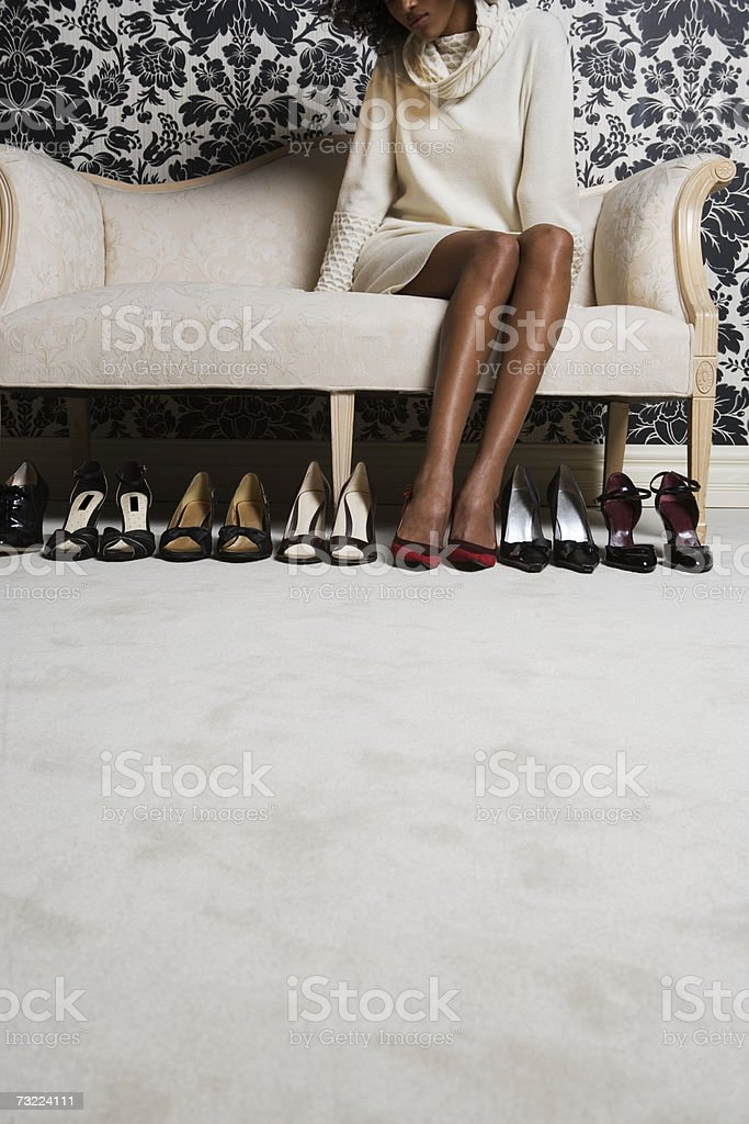 Woman sitting on sofa with pair of shoes on floor, low section stock photo