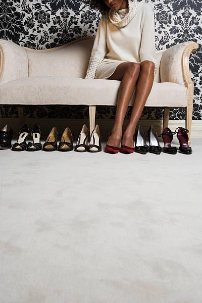 Frau sitzt auf sofa mit passenden Paar Schuhe auf Etage – Foto