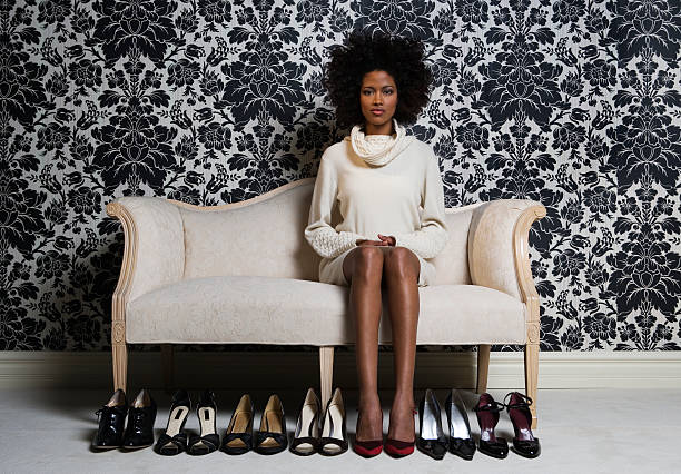 woman sitting on sofa with pair of shoes on floor, portrait - shoes fashion stock photos and pictures