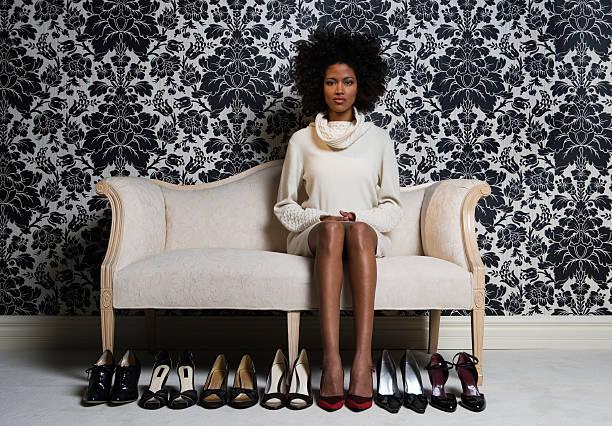 mulher sentada no sofá com um par de calçados para andar, retrato - moda de calçados - fotografias e filmes do acervo