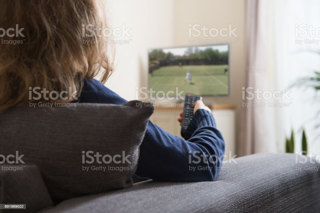 Woman sitting on sofa with remote control in her hand, while watching television in the domestic living room at home stock photo