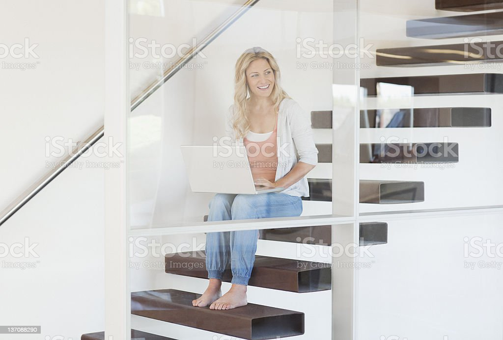 Woman sitting on staircase using laptop royalty-free stock photo