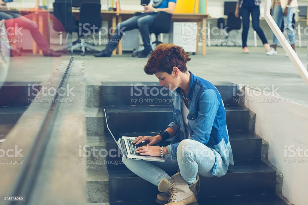 Woman Sitting on stairs and using her laptop. Woman sitting on stairs indoors and using her laptop. Enjoy free WiFi and outsourcing. Creative office or university. 20-29 Years Stock Photo
