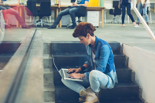 Woman Sitting On Stairs And Using Her Laptop Stock Photo - Download Image Now