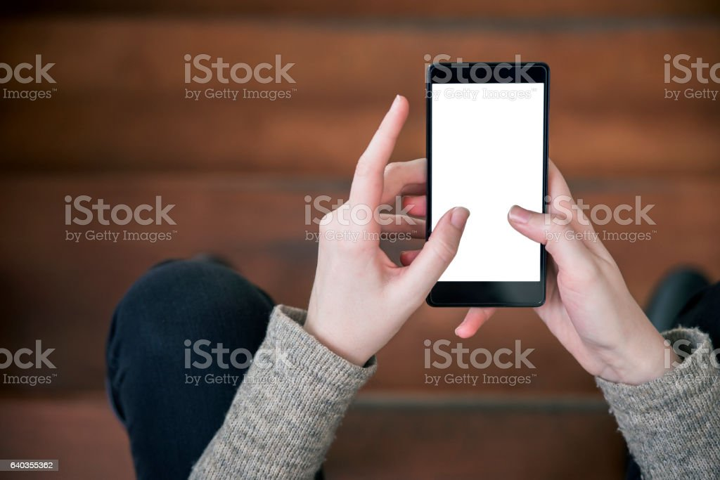Woman sitting on stairs  and using of mobile phone stock photo