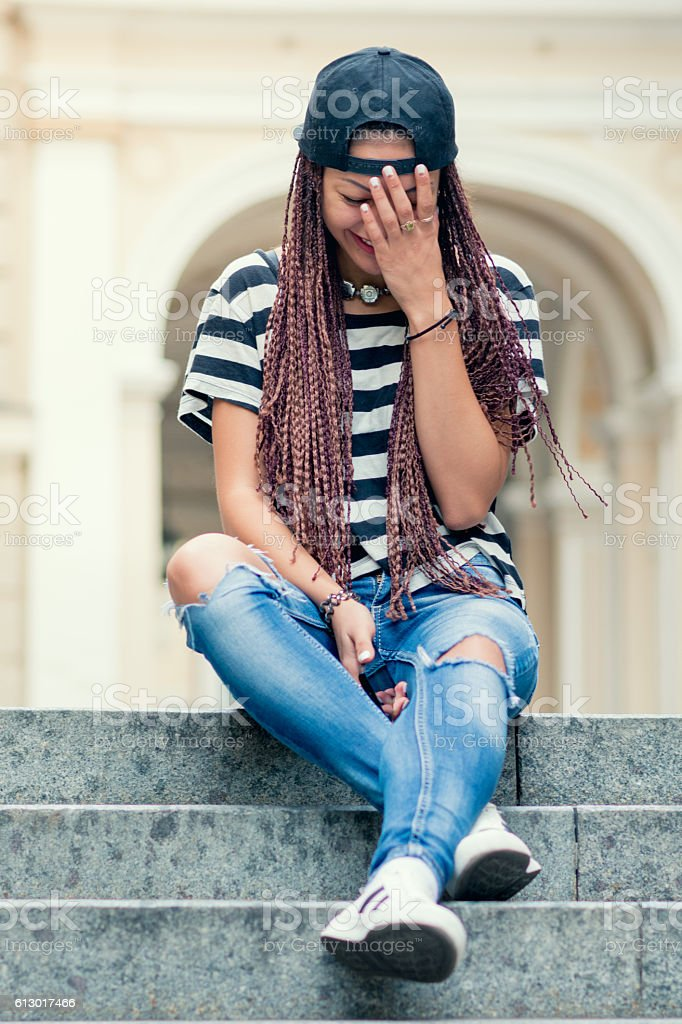woman sitting on stairs, crying and sad stock photo