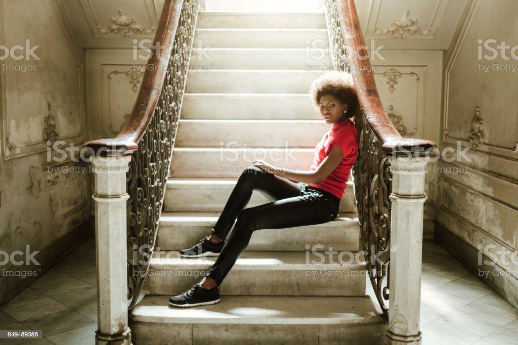 woman sitting on steps at home, Havana, Cuba stock photo