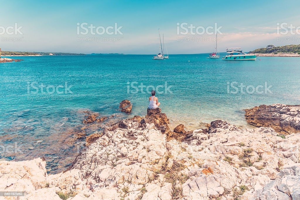 woman sitting on stone at bay of blue croatian sea stock photo