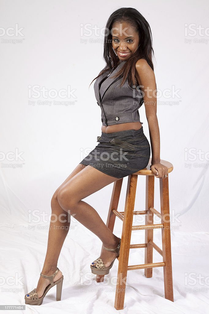 Prime Woman Sitting On Stool And Smiling At The Camera Stock Photo Lamtechconsult Wood Chair Design Ideas Lamtechconsultcom