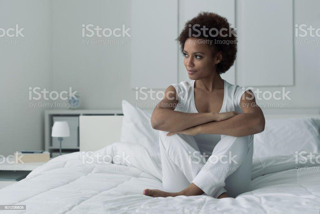Mujer sentada en la cama - foto de stock