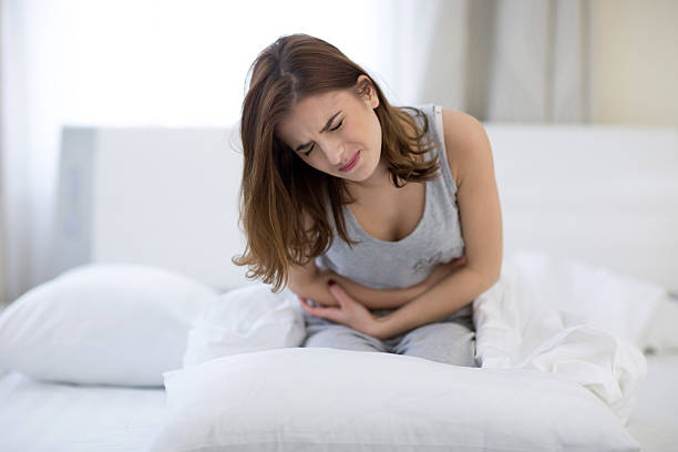 woman sitting on the bed with pain - diarrhea stock pictures, royalty-free photos & images