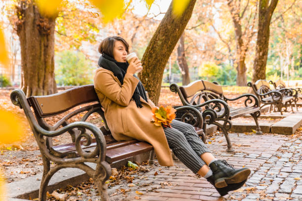 woman sitting on the bench at autumn city park drinking coffee stock photo