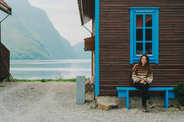 Woman sitting on the bench near the wooden house in Norway stock photo