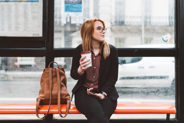 Woman sitting on the bus station stock photo