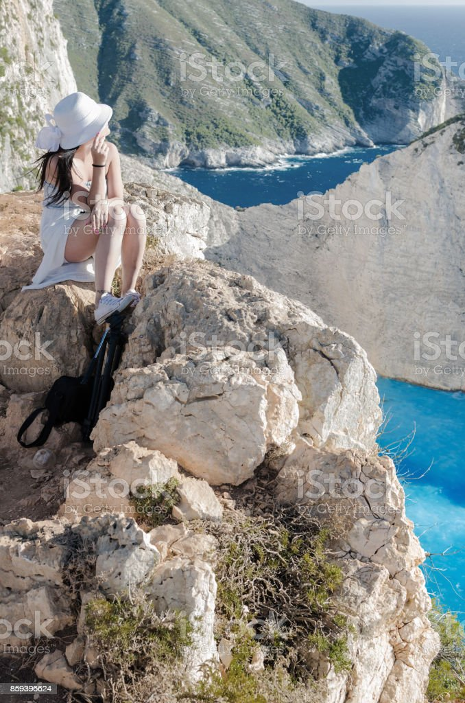 Woman sitting on the cliff at Navagio bech stock photo