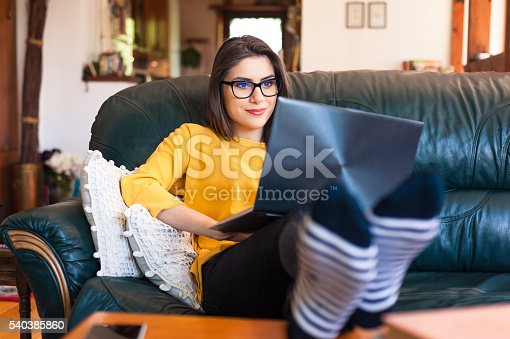 istock Woman sitting on the couch using a laptop. 540385860