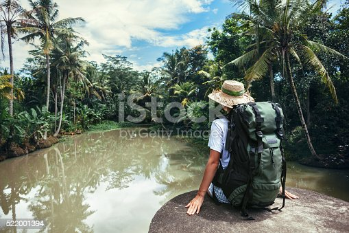istock Woman sitting on the edge near tropical river 522001394