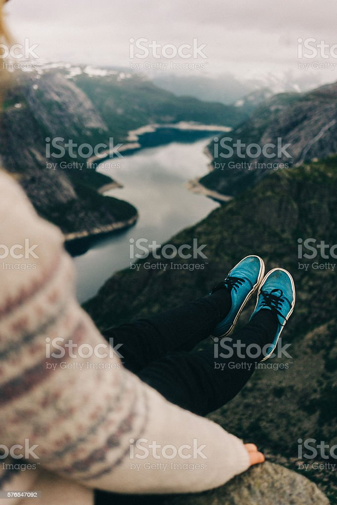 Woman sitting on the edge of Trolltunga stock photo