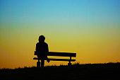 ベンチの丘の夕べに座っている女性