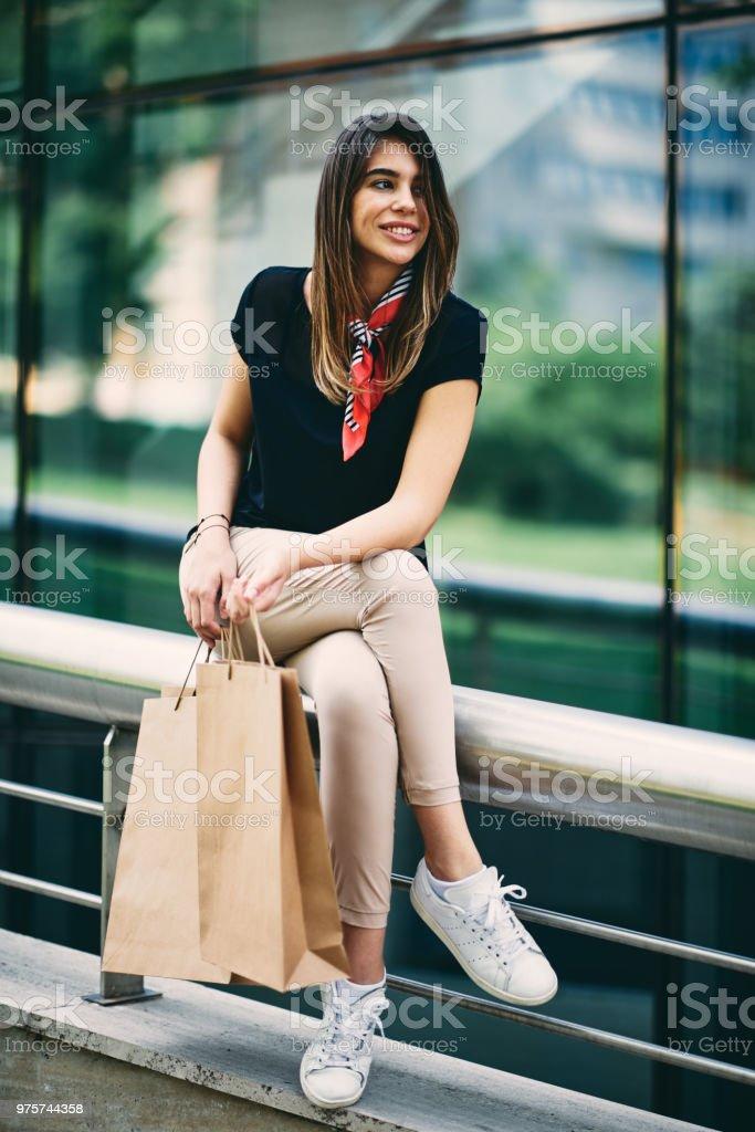 Frau sitzt auf dem Zaun nach dem Einkauf. - Lizenzfrei Attraktive Frau Stock-Foto