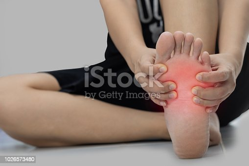 901404510istockphoto Woman sitting on the floor Her hand caught at the foot pain 1026573480