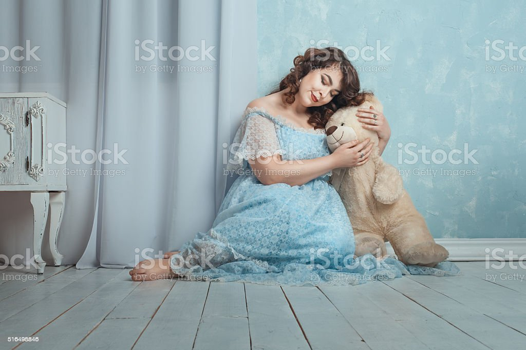 Woman sitting on the floor in a room with toys. stock photo