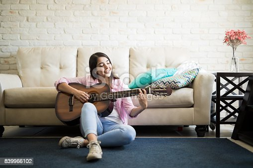 istock Woman sitting on the floor playing guitar 839966102