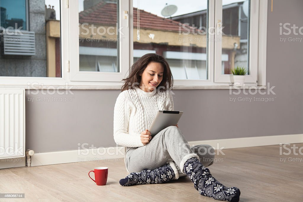 Woman sitting on the floor using a touch screen tablet stock photo