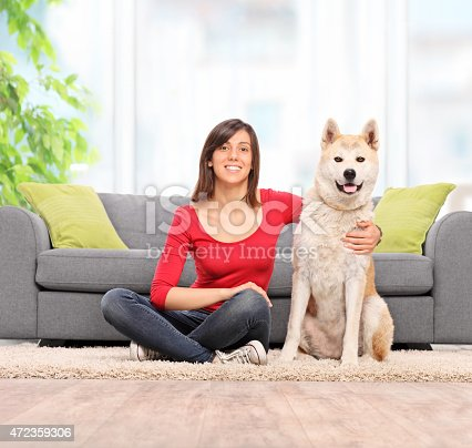 istock Woman sitting on the floor with her pet dog 472359306