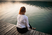 Top view of young woman sitting on pier next to the wather, looking away