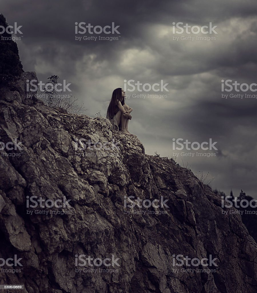 Woman sitting on the rock against sullen sky stock photo
