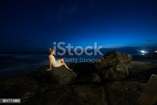 istock Woman sitting on the rock at dusk. 904714960