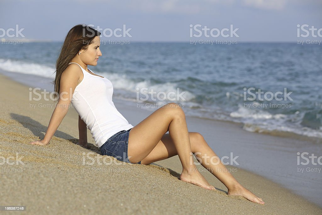 Woman sitting on the sand of a beach stock photo
