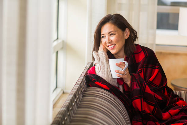 Woman sitting on the sofa drinking coffee. stock photo