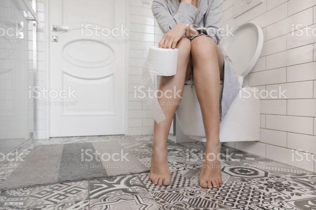 Woman sitting on the toilet holding toilet paper stock photo