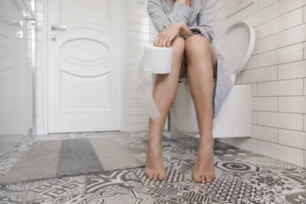 woman sitting on the toilet holding toilet paper - constipation stock pictures, royalty-free photos & images