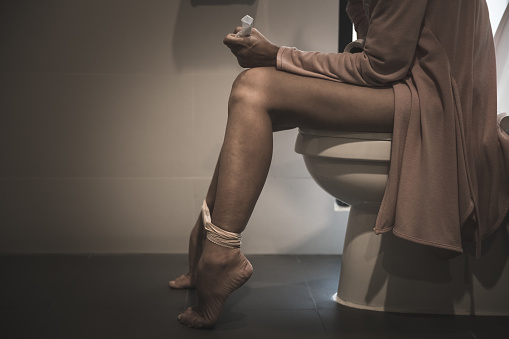 Girl sitting on toilet bowl and wearing virtual reality