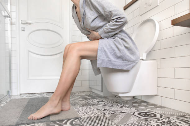 woman sitting on toilet holding her stomach - constipation stock pictures, royalty-free photos & images