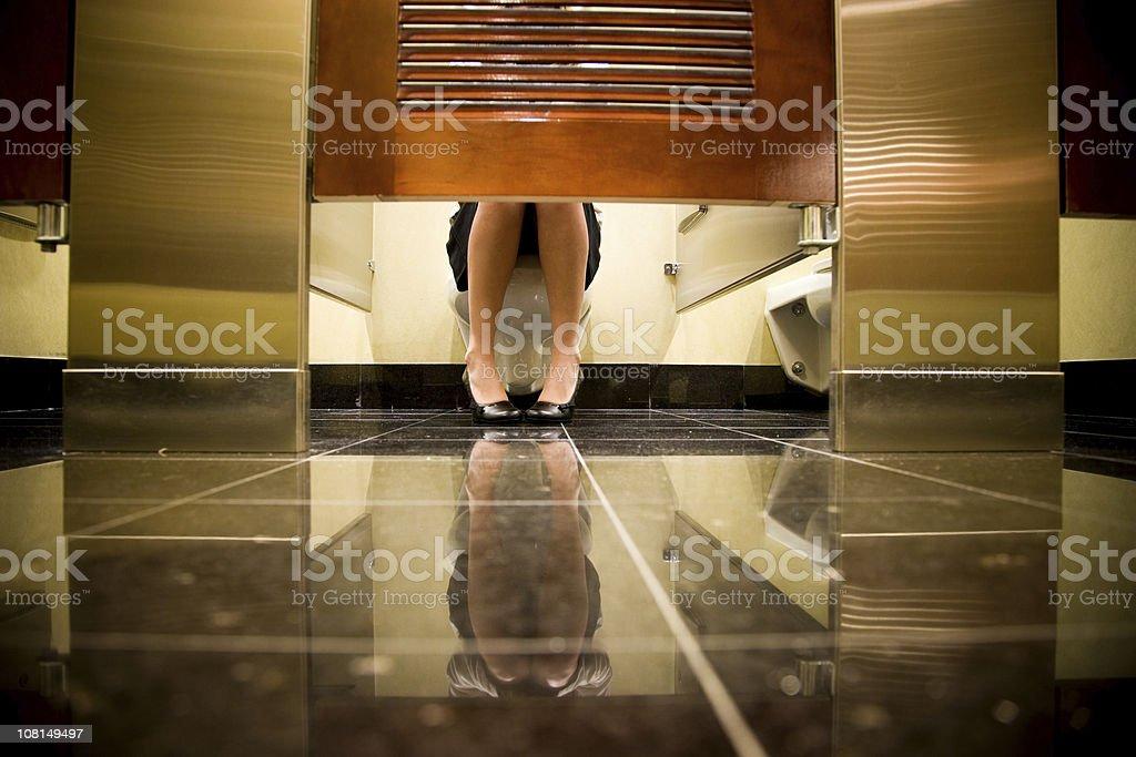 Woman Sitting on Toilet stock photo