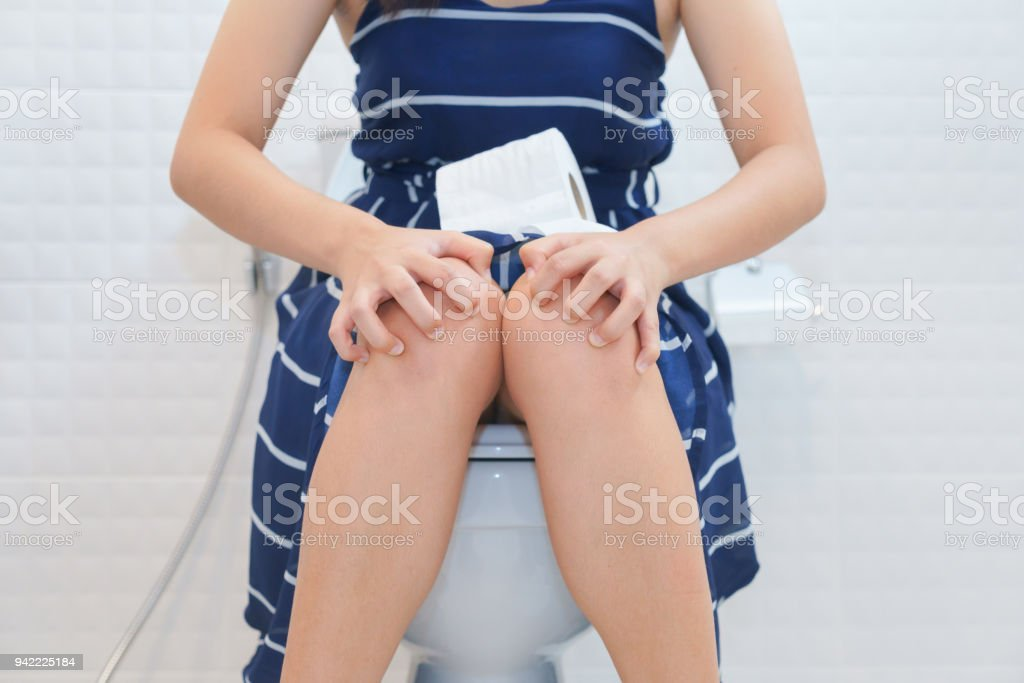 Woman sitting on toilet with toilet paper - constipation concept stock photo