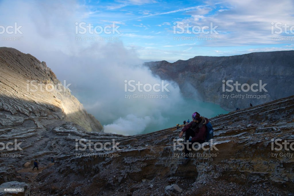Woman sitting on top of crater Mount Kawah Ijen volcano. stock photo