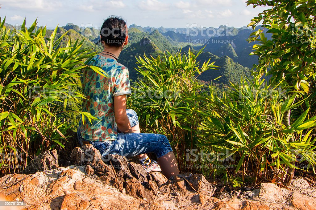 Woman sitting on top of the mountain stock photo