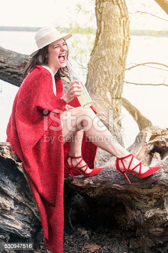 873264516istockphoto woman sitting on tree with bottle of champagne 530947516