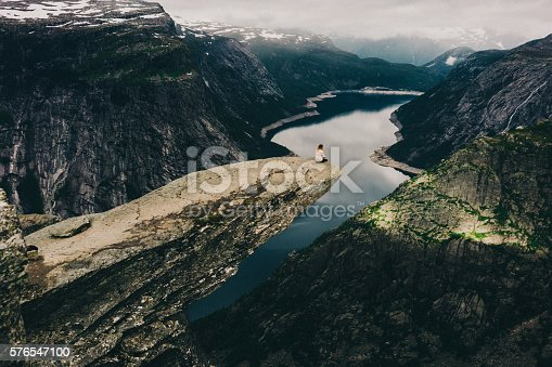 Woman sitting on the edge of the Trolltunga rock