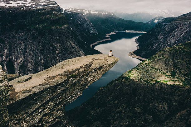 Woman sitting on Trolltunga Woman sitting on the edge of the Trolltunga rock  ravine stock pictures, royalty-free photos & images