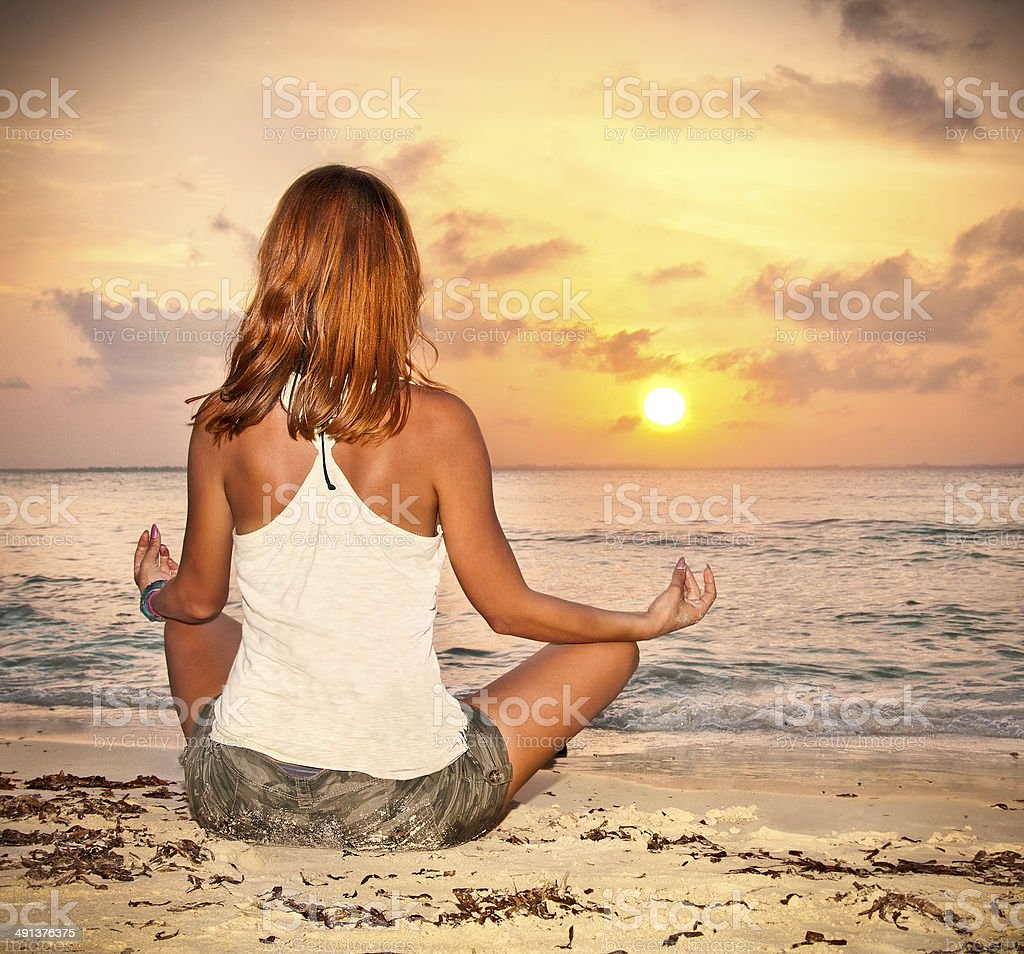 Woman Sitting On Tropical Beach At Sunset Stock Photo